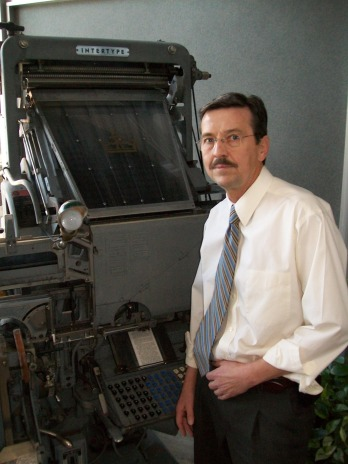 """THE PERFECT PRINT Star Phoenix Editor in Chief Steve Jibb stands next to a Linotype, one of the oldest printing presses in the world. In the 60s it was the newsroom's linchpin- now it's on display in the newspaper's lobby, perhaps one day as big an artifact as the publication it used to print. But Jibb doesn't see it that way, """"People have been saying the newspaper will die for years,"""" he said in a near huff. """"According to them, it was supposed to happen 10 years ago. But they're still holding on."""""""